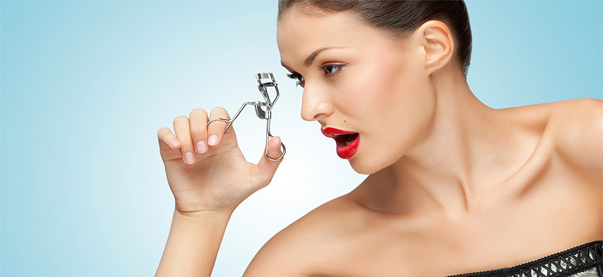 woman holding eyelash curler near eye